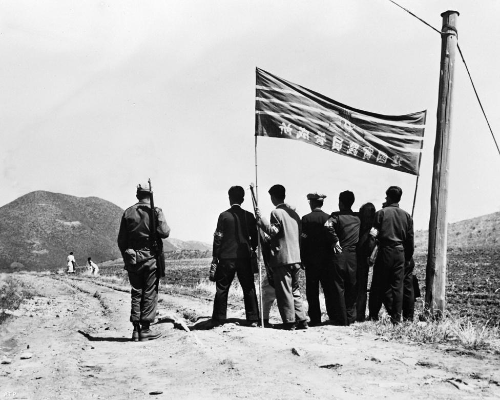 1948. augusztus, egy amerikai katona, és dél-koreai civilek a világháborút lezáró potsdami konferencián a két ország határvonalaként elfogadott 38. szélességi körnél. A háttérben a két alak észak-koreai földműves.
