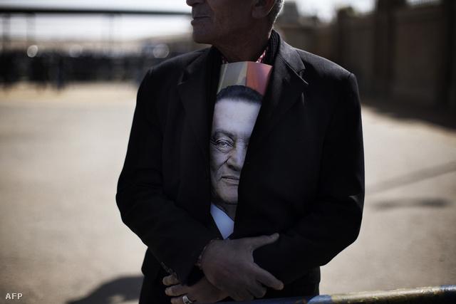 Hoszni Mubarak támogatója várakozik a bukott egyiptomi elnök pere alatt a kairói bíróság előtt február 22-én