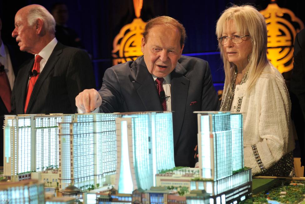 A Venetian komplexumok tulajdonosa, Sheldon Adelson Las Vegas-i                          kaszinómogul és felesége egy Makaóba tervezett újabb épületegyüttes                          makettjével. A befektetők sorra húzzák fel az egyre nagyobb luxust kínáló                          kaszinóikat, amik közül több korábbi mocsaras területek feltöltésével                          épülhetett meg.
