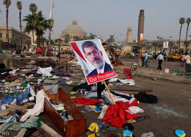 Mohamed Murszi megdöntött egyiptomi elnököt ábrázoló plakát az elnököt támogató tüntetők táborának maradványai között