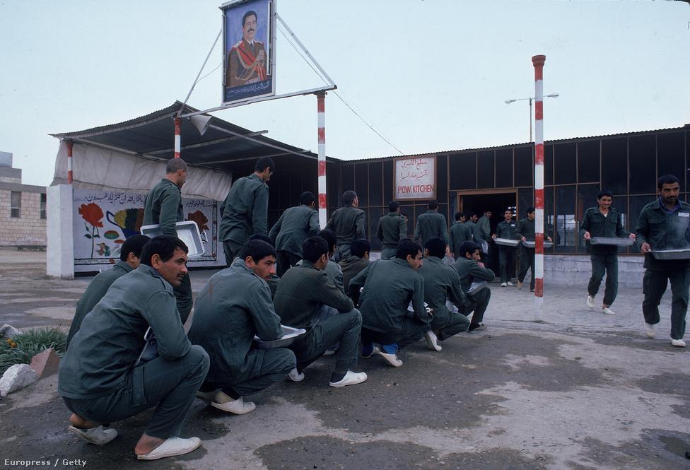 Ételre váró iráni hadifoglyok Irakban, Szaddám Huszein mosolygó portréja alatt. A háború 1988-as befejezése után két évvel kezdte el a két ország kölcsönösen elengedni a foglyokat.