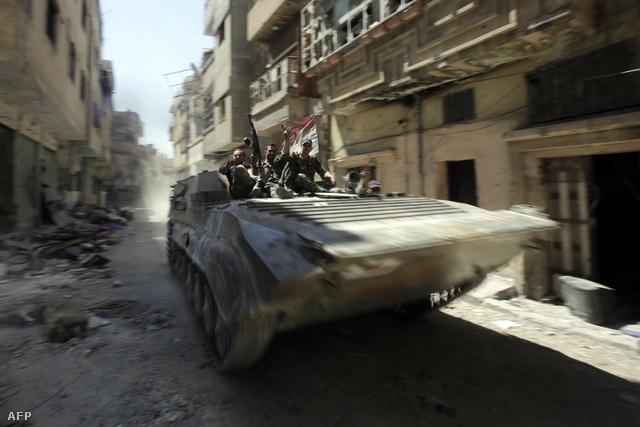 A szíriai hadsereg egyik harckocsija járőrözik egy szétlőtt utcán Homszban