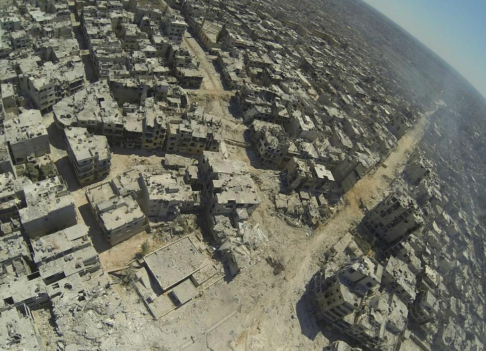 Homszot a kormány hatalmas erőkkel                          bombázta, ahogy ez a városról készült légi                          felvételen is látszik. A kép a Kalidija                          negyedben készült, amit a rezsim július végén foglalt vissza a felkelőktől. A posztapokaliptikus sivatagban az épületekből szinte csak a falak maradtak meg.
