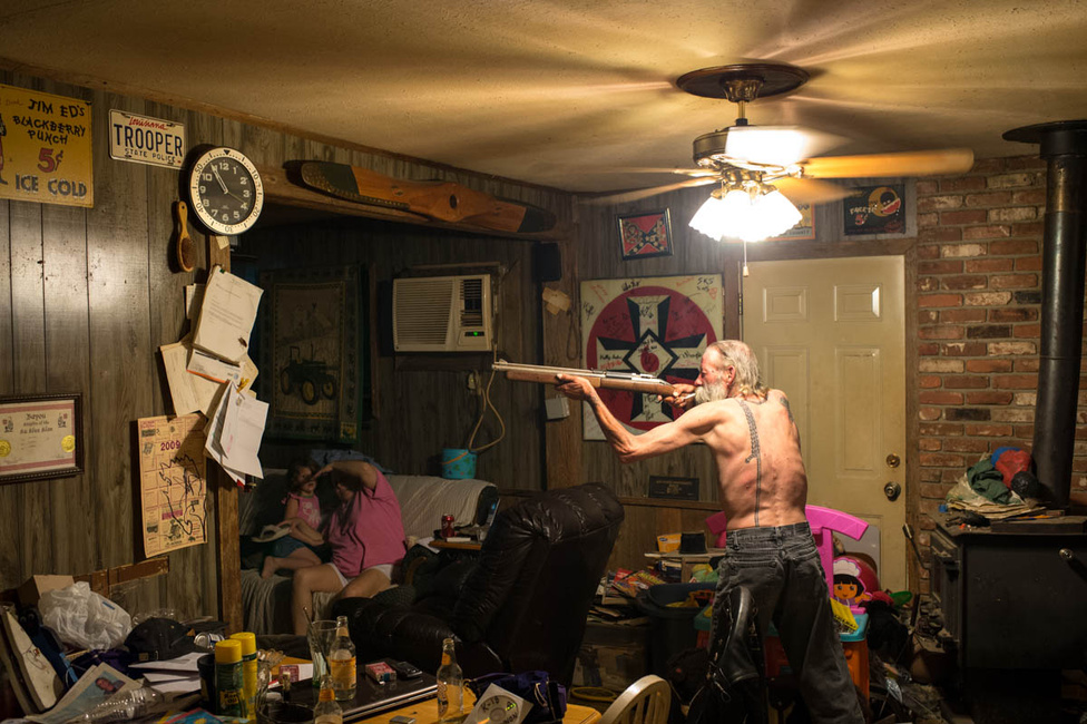 Carl, a Klán egyik déli állambeli csoportjának vezetője, azaz Birodalmi Varázslója egy gigászi csótányt (az óra alatti papíron az a fekete folt) készül leszedni légpuskával. A háttérben a felesége és a keresztlánya.