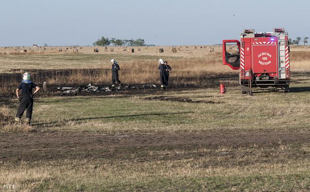 Tűzoltók dolgoznak egy lezuhant kisrepülő roncsai mellett Nádudvarnál