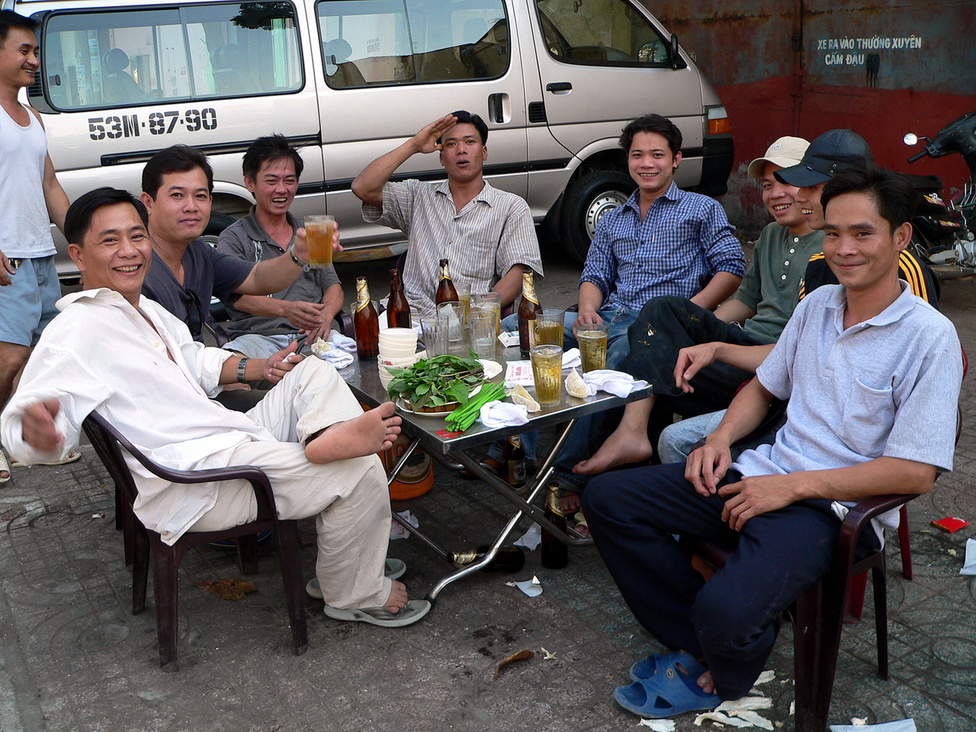Szieszta ebédidőben, a járda közepén, Ho Si Minh-város kínai negyedében. A forró leves után jólesik a hideg sör a nagy melegben, és még jobban az európai turistával való évődés. Aki állja a tréfálkozást, amiből szerencsére egy szót sem ért, annak kijár egy meghívás az asztalhoz, és egy üveg folyékony kenyér.
