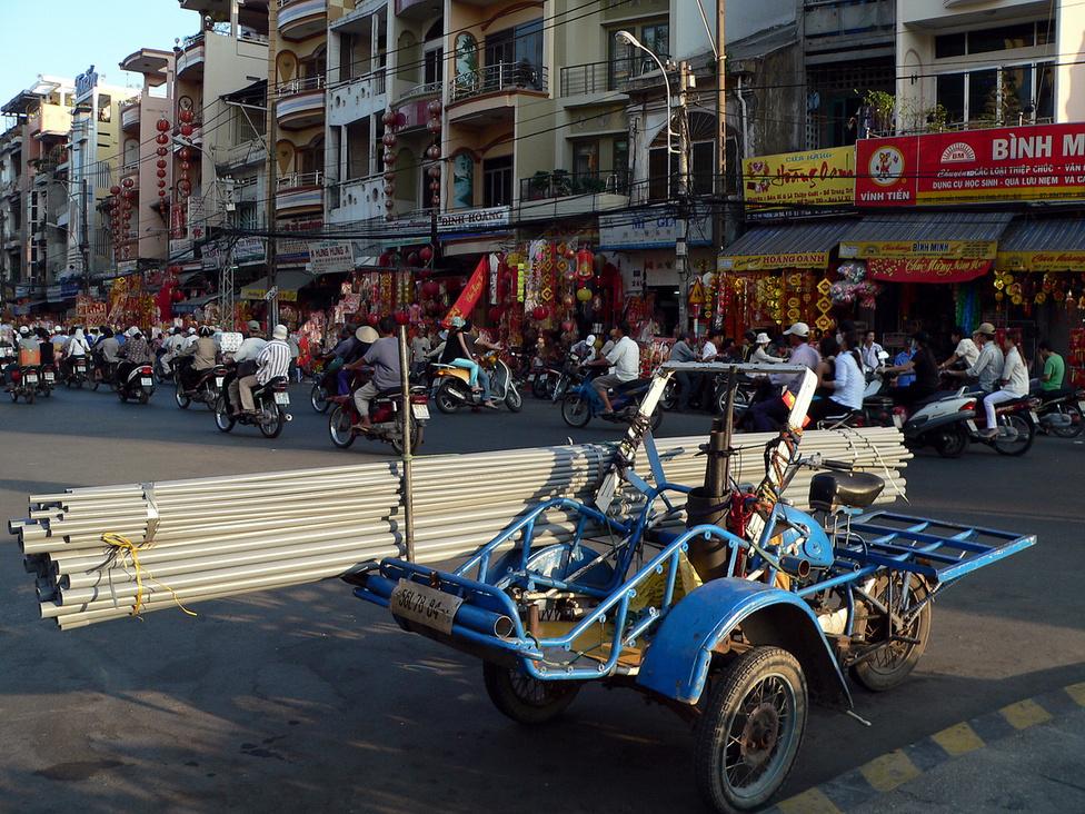 Célszerszám. Teherhordásra, fuvarozásra építették ezt a masszív vázú triciklit, amelyre sokféle árut fel lehet pakolni és rögzíteni. Mint az összehajtogatott tetőváz mutatja, személyszállításra is pillanatok alatt átalakítható pár mozdulattal és az ülések visszahelyezésével. Az efféle járgányok jobban boldogulnak a forgalomban, mint a teherautók, és a szűk utcákba is be tudnak hajtani, így kisebb árumennyiségek rövidtávú fuvarozásra kiválóak.