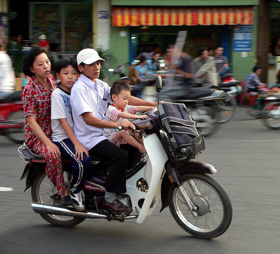 Honda Dream, a megvalósult álom. Autó híján a robogók a legtöbb családban mindenes járműként szolgálnak, és egyúttal univerzális munkaeszközök is a legtöbb kisvállalkozásban. Mindent visznek, öt malactól nyolcvan műanyag marmonkannáig, és egy négy-ötfős család simán elfér rajtuk. Ezek a csöppségek motorizálták Vietnamot, és kilométerek millióit teszik meg naponta a Magyarországnál közel négyszer nagyobb országban.