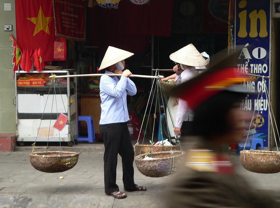 Mozgóárusok Hanoi belvárosában. Bár a gazdaságban egyre nő a külföldi befektetők és a helyi magánvállalkozók szerepe, a politikában a Vietnami Kommunista Párt szilárdan őrzi pozícióit. A vietnami zászló piros-arany színe nemcsak a kommunista berendezést jelképezi: ez a két szín, akárcsak a szomszédos Kínában, itt is a jólét, a boldogság és a szerencse szimbóluma.