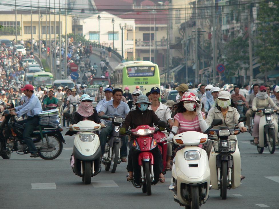Délutáni csúcsforgalom Saigon belvárosában. Az ország gazdasági központjában mintegy hárommillió robogó pöfög az utakon. A közlekedési szabályokra a többség inkább csak egyfajta javaslatként tekint, bár a piros lámpánál azért megállnak. Gyalogosoknak viszont szinte soha, ezért az átkelés technikája a következő: lassan, de határozottan el kell indulni, és megállás nélkül átmenni a másik oldalra. A robogók áradata lassítás nélkül megnyílik, majd bezárul. A gépkocsik sajnos megzavarják ezt a szisztémát, mivel a motorosok nem látják tőlük az életéért küzdő gyalogost – úgyhogy a gyalogos közlekedésben a szerencsefaktor szerepe egyre erősödik.