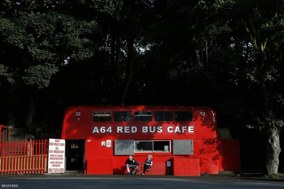 Észak-Anglia, Thorner, A64-es út mentén.                         Jay Grey és húga, Vicky várják az ebédjüket  az emeletes buszból átalakított a Red Bus Kávézó előtt.