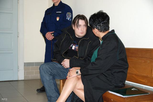A kényszervallatás és halált okozó testi sértés gyanúja miatt őrizetbe vett két izsáki rendőr egyike várakozik az előzetes letartóztatásról döntő ülés előtt a Kecskeméti Városi Bíróság folyosóján 2013. április 11-én.