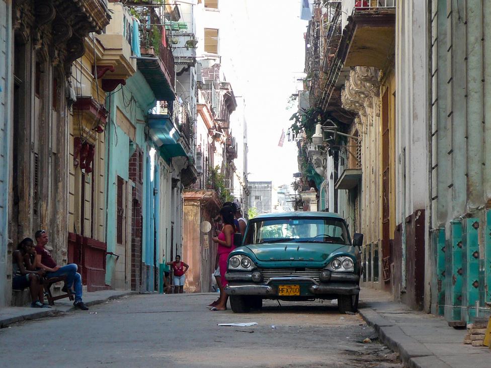 Nem csak autók vannak, megvan hozzá a tökéletes háttér is. Csak ki kell menni az utcára, és mire kétszer megpróbáltak eladni nekünk kamu Cohibát, biztosan beleszaladunk egy ilyen jelenetbe. Ez a giccs maga a hétköznapi szürkeség Centro Havanában, ami ott a Nyócker és a Belváros fura katyvasza.