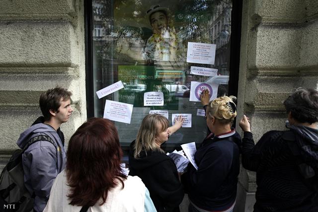 Tüntetők ragasztgatnak feliratokat egy belvárosi bankfiók ablakaira, egy devizahitelek eltörlését követelő demonstráción