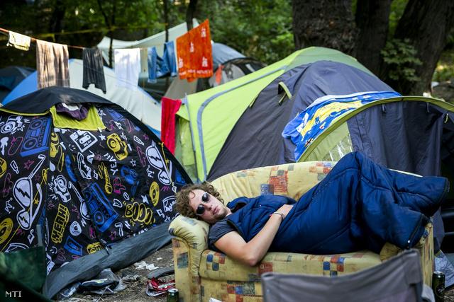 Egy fesztiválozó alszik a sátra mellett az idei Sziget utolsó utáni napján