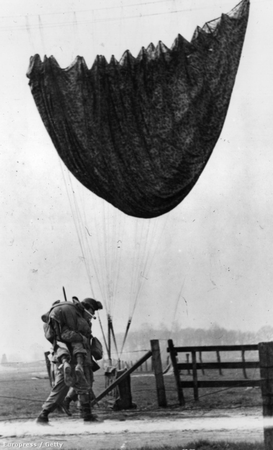 Társán segítő katona.                         Egy katonai ejtőernyős az amerikai hadsereg 17. légi szállítású hadosztályából segíteni próbál sérült társán, akit az elsősegély-állomásra igyekszik eljuttatni Wesel közelében a rajnai átkelés biztosításakor. Egy ejtőernyő lóg egy távíróvezetéken.