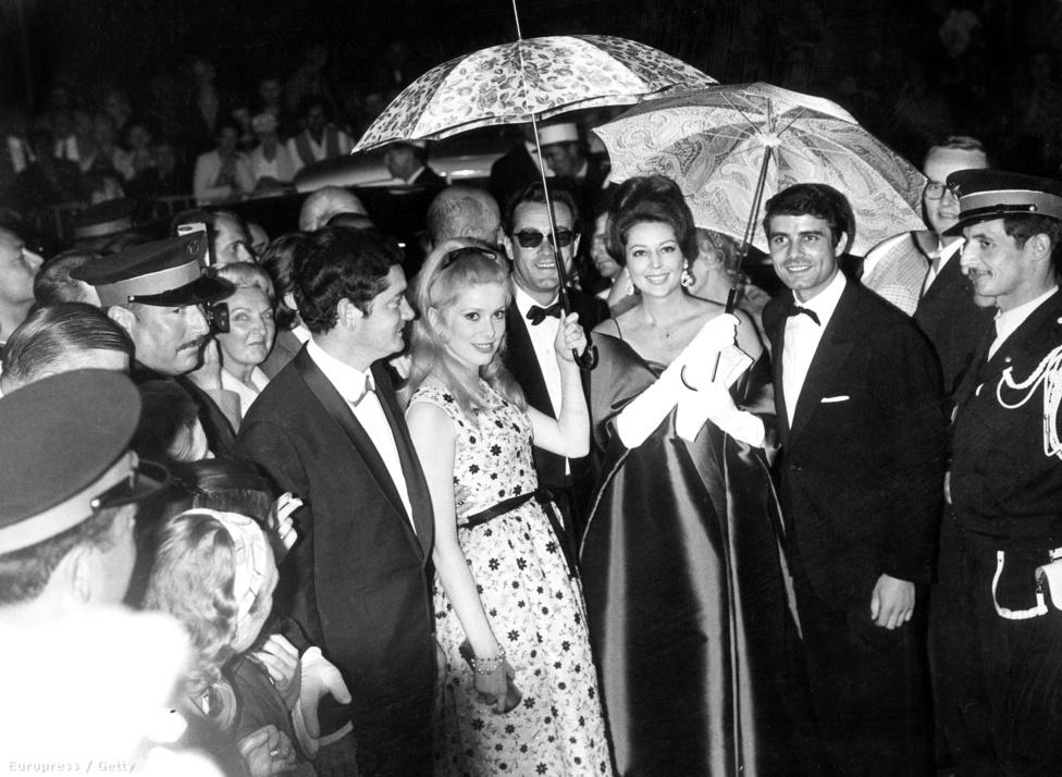 A színésznő Jaques Demy rendezővel, Michel Legrand zeneszerzővel, Anne Vernon színésznővel és Nino Castelnuovo olasz színésszel az 1964-es Cannes-i Filmfesztiválon. A Cherbourgi esernyők című filmet népszerűsítik, ami meghozta a világhírt Deneuve-nek. Geneviéve-et, egy esernyőboltban dolgozó lányt játszik, akit anyja eltilt a szerelmétől, ráadásul a fiút elviszik katonának.