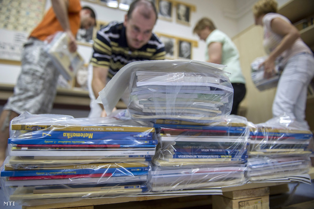 A békési Dr. Hepp Ferenc Általános Iskola és Alapfokú Művészeti Iskola tanára tankönyveket pakolnak 2013. augusztusában, miután kiszállították a tankönyvek egy részét.