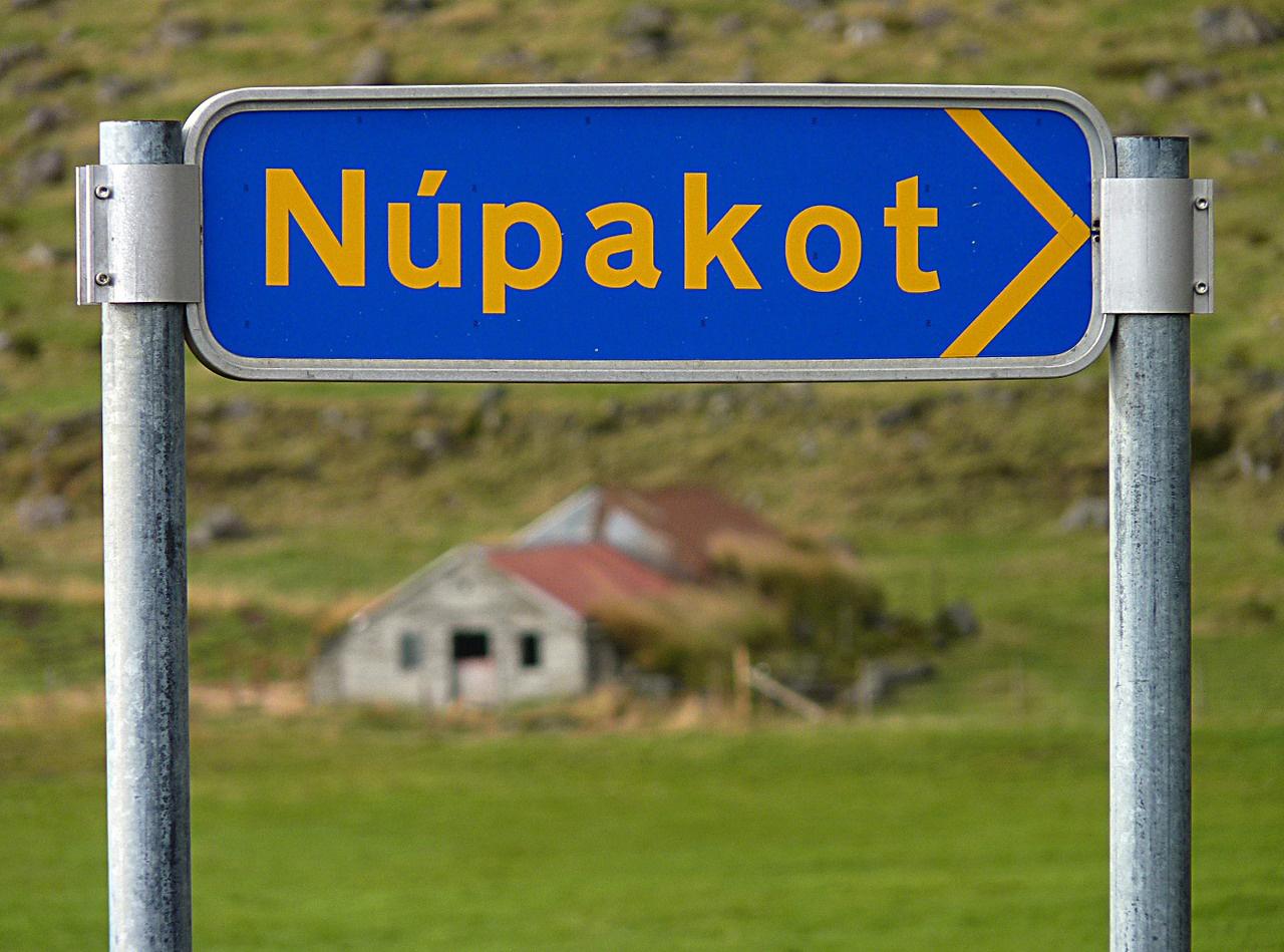 Település kezdetét jelző tábla. Núpakot nevét könnyű memorizálni, de mit szólnak például ehhez: Kirkjubaearklaustur? Magyar füllel az északi nyelvekkel rokon izlandi követhetetlen, és a legtöbb földrajzi név első hallásra-látásra megjegyezhetetlen. Az izlandiak féltő gonddal óvják a nyelvüket, ugyanakkor szinte mindenki folyékonyan beszél angolul – nagyon sokan pedig felsőfokon