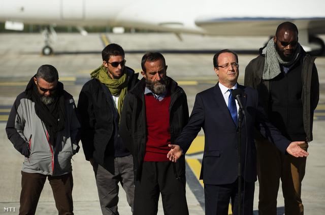 Francois Hollande francia elnök a három év után Nigerből kiszabadult francia túsz Marc Feret (b), Pierre Legrand (b2), Daniel Larrible (b3), és Thierry Dol (j) társaságban a Párizs közelében fekvő Vélizy-Villacoublay katonai bázison
