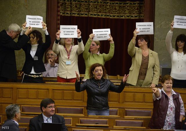 """A széksorok között a DK független képviselői, Vadai Ágnes alelnök (j2) és Szűcs Erika (j). Mellettük Veres János szocialista képviselő (b2). Vadai Ágnes az akció után Facebook-bejegyzésben tudatta: az ellen tiltakoztak, hogy """"az asszonyverő Balogh József még mindig képviselő és polgármester lehet""""."""