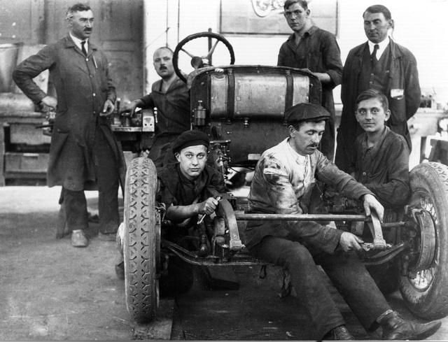 Az első hathengeres, a Magomobil Six szerelése 1926-ban. Jól láthatók a Lockhead hidraulikus szalagfékek, a bejáratáshoz szerelt benzintartály és az első váztagok keresztmerevítője, amelyet később elhagytak. Balra Schlederer József próbaüzem-vezető (Fotó: Collection Burányi)