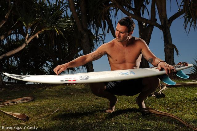Ausztrália szörfbajnoka az óceánparton pózol
