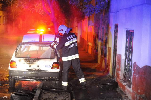 Tűzoltó dolgozik egy személyautóban keletkezett tűz oltásán a XX. kerületi János utcában 2013. november 16-án. A tűzben egy ember súlyos égési sérüléseket szenvedett.