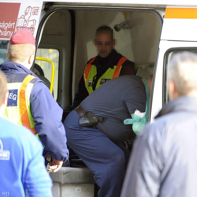 Rendőrök között ül egy mentőautóban 2013. november 16-án a főváros XVII. kerületében az a férfi aki gázriasztópisztollyal lőtt rá munkásokra.