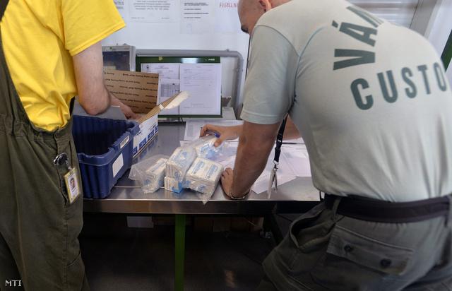 Külföldről érkezett gyanús gyógyszereket tartalmazó csomagokat vizsgál egy vámos.