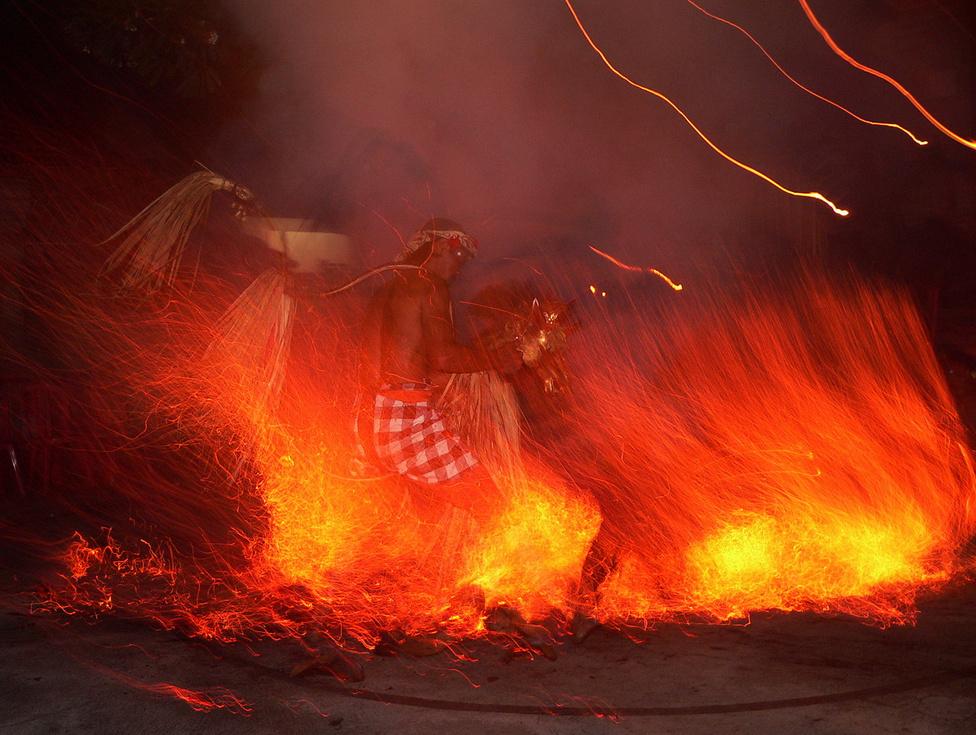 Bali hindu zárványként létezik a túlnyomó részt iszlám Indonéziában. Szépérzékkel megáldott lakói magas szinten művelik az építészetet, a kézművességet, a kertészkedést, a zenét és a táncot. Képünk a sziget művészeti központjának számító Ubudban készült, ahol a táncosok – akik többnyire nem hivatásos művészek, hanem a város lakói, akik napközben a földeken, a műhelyekben, az üzletekben dolgoznak – tűztáncot mutatnak be, mezítláb ugrálva a parazsakon