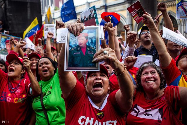 Nicolas Maduro venezuelai elnök támogatói ünnepelnek a nemzetgyűlés caracasi épülete előtt 2013. november 19-én miután a parlament elfogadta az elnököt rendeleti úton való kormányzásra falhatalmazó törvényt.