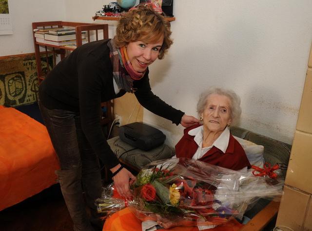 Terézváros polgármestere, Hassay Zsófia egy óriási virágcsokorral köszönti a kerület egyik idős polgárát.