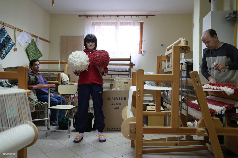 """A három férfinak október 30-án volt az utolsó munkanapja Lesencetomajon. Az intézetben a Fővárosi Kézműipari Kht. foglalkoztatja a lakók egy részét. Van, aki szivacsot aprít, van, aki sző vagy varr, van, aki kerámiákat készít. A lakók reggel 8-tól négy órában dolgoznak, és havonta nagyjából 40 ezer forintot keresnek, ám jövedelmük 30 százalékát elviszi az intézményi térítési díj. Aki viszont nem tud fizetni, azt is ugyanazon a szinten, egyenlő szolgáltatásokkal látják el, mint a fizető lakókat. Sokan a kastély körüli munkálatokat látják el, gondozzák a parkot, a kertet, segédkeznek a konyhán, a mosodában. Korábban előfordult, hogy külső munkákat is szerveztek nekik, nyáron például almaszedést, ám az ilyen munkalehetőség meglehetősen ritka. A legfiatalabb lakó az intézményben 20 éves, a legidősebb 83, akinek 106 éves édesanyja a mai napig rendszeresen telefonál. Annyi kérése volt csupán az intézményvezető felé, hogy fiát Janikának szólítsák, és gondoskodjanak arról, hogy ha hideg az idő, a fián mindig legyen füles sapka.                                                   A képen jobb oldalt látható Zoltán éppen egy fehér-piros szőnyeget készít vasúti sorompó stílusban. Neki is felkínálták a lehetőséget, hogy idén novembertől Lesencetomaj helyett Tapolcán dolgozhasson, az Életlehetőség szociális nappali intézményben. Átgondolta, el is ment az első munkanapján az új helyre, majd másnap visszatért Lesencetomajba. """"A drapp, gyapjú anyag a kedvencem. Furcsa lenne, ha nem járnék Tomajra, és nem szőnék szőnyeget"""" – mondja, miközben szakszerű mozdulatokkal illeszti a vékonyra hasogatott rongycsíkokat a lesencetomaji szövőszék húrjai közé. Üvölt a mulatós zene, Zoli itt érzi jól magát.                                                    Horváthné Somogyi Ildikó, a Veszprém Megyei ÉFOÉSZ vezetője elfogadta Zoltán döntését, semmit nem akar siettetni a három férfi életében. """"Egymásnak feszül ebben a helyzetben két dolog, az egyik, hogy szeretnénk, ha mindhárman függetlenednének az"""