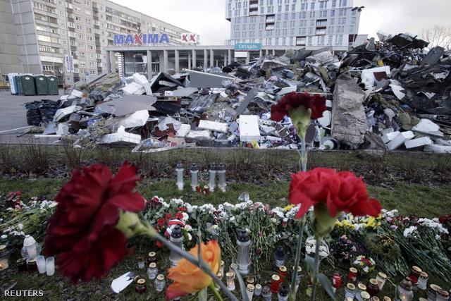 Virágok a rigai szupermarket előtt, amelynek a tetőszerkezete beomlott, 54 ember halálát okozva
