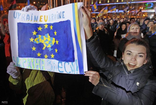 Tüntetők egy EU-zászlót ábrázoló plakáttal az Ukrajna európai integrációjának leállítása miatti tiltakozáson a kijevi Európai téren 2013. november 26-án.