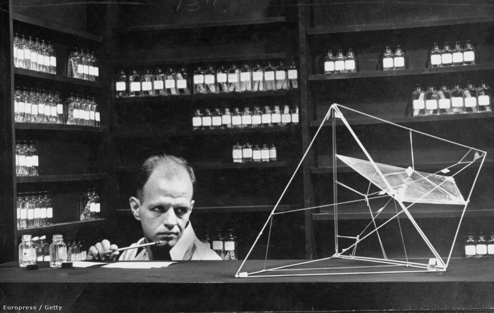 Douglas Slocombe tudós egy olyan huzalpiramisra mered, amely a műanyag szerkezetét illusztrálja.