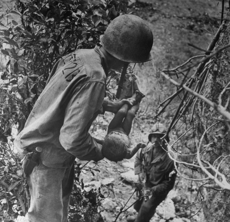 W. Eugene Smith-t a világháborús fotói tették igazán ismertté. Ezen a képen egy amerikai tengerészgyalogos egy súlyosan sérült csecsemőt ringat a második világháború japán frontján. A kis testet arccal lefelé találták egy barlangban, ahova a japánok az amerikai támadások elől húzódtak be. Smith nagyon elkötelezett fotós volt, az Okinawa-i ütközet után 12 ezer mérföldet stoppolt Guamba, hogy minél hamarabb eljuttassa a képeket a Life szerkesztőségébe, majd az első géppel repült vissza a frontvonalra