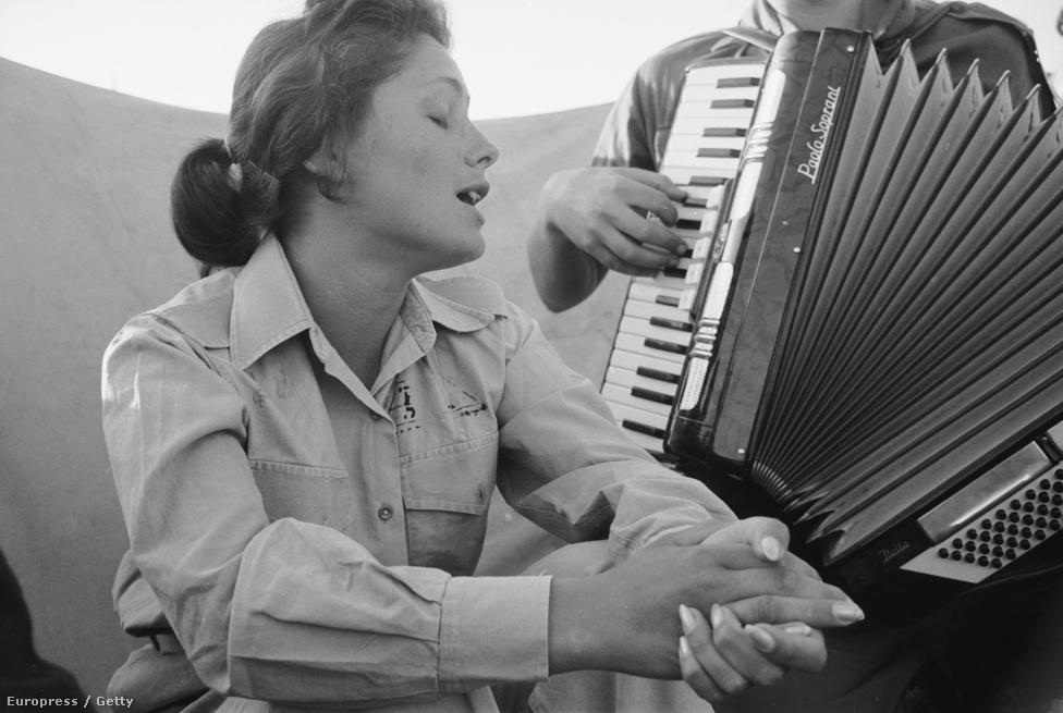 Fiatal izraeli nő énekel, miközben harmónikán kísérik.