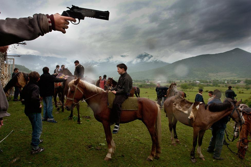 Csecsen gyerekek játékfegyverekkel ünneplik a függetlenség napját Grúziában. Ez a menekültek ünnepe: családjuk ezen a napon hagyta el az Oroszországgal két vesztes függetlenségi háborút vívó Csecsenföldet. 13 éve, hogy legalább ötezer csecsen menekült érkezett a határ grúz oldalára, a Pankisi-völgybe. A háborús pusztítások elől menedéket keresőket Moszkva terroristának bélyegezte, miközben ők hivatalos papírok és a munka esélye nélkül éltek szülőhelyüktől 100 kilométerre. Daro Sulakuari grúz fotóriporter félévet töltött el itt. A részben csecsen származású fotós együtt élt a menekültekkel, ebből született a most látható képeket tartalmazó Terra Incognita sorozata.
