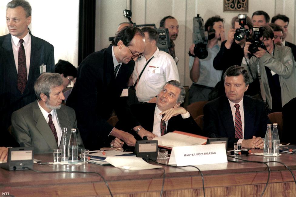 Jeszenszky Géza külügyminiszter, Antall József miniszterelnök és Somogyi  Ferenc, a külügyminisztérium államtitkára a Varsói Szerződés (VSZ) megszűnését hozó VSZ Politikai Tanácskozó Testületének záróülésén 1991 július 1-jén. Antall úgy érezte, neki volt a legnagyobb szerepe a kommunista tömb katonai együttműködésének megszüntetésében (ekkor még létezett a Szovjetunió), mivel a többiek csak átalakítani akarták a szervezetet. Végül Gorbacsov – akivel Antallnak mindvégig jó kapcsolata volt – rábólintott Antall javaslatára. A miniszterelnöknek fájt, hogy a magyar ellenzék szerint tönkretette a magyar–szovjet kapcsolatokat, különösen sérelmezte Horn Gyulának azt a nyilatkozatát, hogy ő a parlament külügyi bizottságának elnökeként azért utazott el Moszkvába, hogy helyrehozza az Antall által elrontott viszonyt. Érdekesség, hogy a képen látható Somogyi már a rendszerváltás előtti Németh-kormányban is külügyi államtitkár volt, habár Antall a választási győzelem után azt nyilatkozta: az előző kormányok miniszterei, államtitkárai nem lesznek az új kabinet tagjai. Somogyi Ferenc Gyurcsány Ferenc első miniszterelnöksége idején külügyminiszter lett.