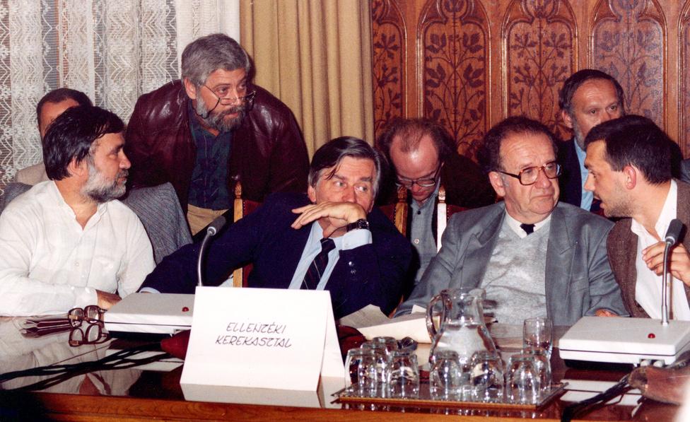 """Nemzeti Kerekasztal-tárgyalások. Horváth Balázs hajol oda Antall Józsefhez, aki mellett Szabad György és Orbán Viktor ül. 1989 júniusában állapodott meg az Ellenzéki Kerekasztal, az MSZMP, valamint a legkülönfélébb társadalmi szervezetek és csoportok arról, hogy Nemzeti Kerekasztal (NKA) néven tárgyalásokat kezdenek az ország alkotmányos rendszerének átalakításáról. Antall szerint az NKA jelentősége abban állt, hogy az ellenzéki szervezetek kiléptek a szűken vett ellenzékiségből, kénytelenek voltak szakértőket keresni. Így lett MDF-es Balsai István későbbi igazságügy-miniszter. Antall itt elmondott egy nagy beszédet arról, hogyan jutott a negyvenes évek második felében demokráciából diktatúrába az ország. A beszéd végén sajátos tetszésnyilvánításként Orbán lehajolva verte az asztalt: """"Padlón vannak a kommunisták!"""""""