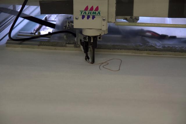...és ide jut. Ami közötte van, az titkos. Ipari hímzőgépek vannak átalakítva a feladathoz.