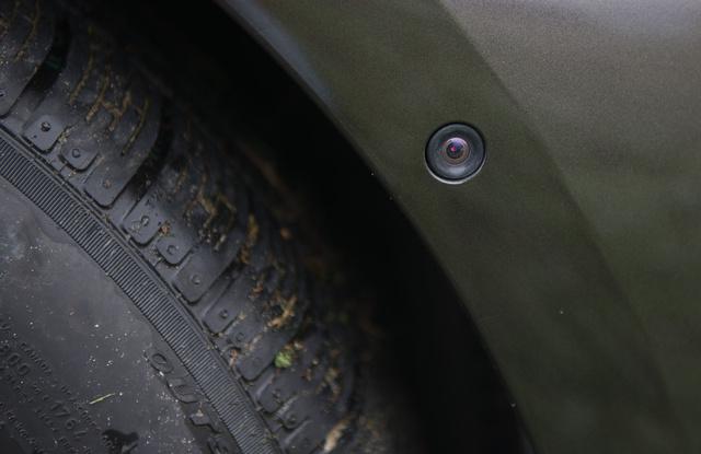 Kereszteződésbe kukucskáló kamera az első kerékív elején