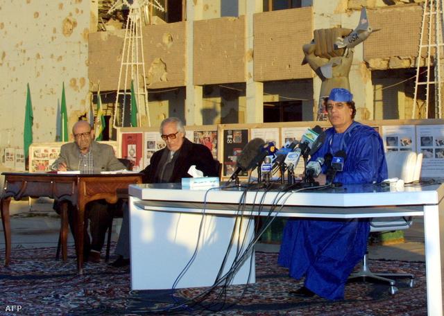 Kadhafi és ügyvédei sajtótájékoztatót tartanak 2001-ben egy 1986-ban lebombázott épület előtt, ahol bejelentették, hogy nem fizetnek kártérítést a merénylet áldozatainak, amíg az USA sem fizet a mögöttük látható házban meghalt áldozatok hozzátartozóinak