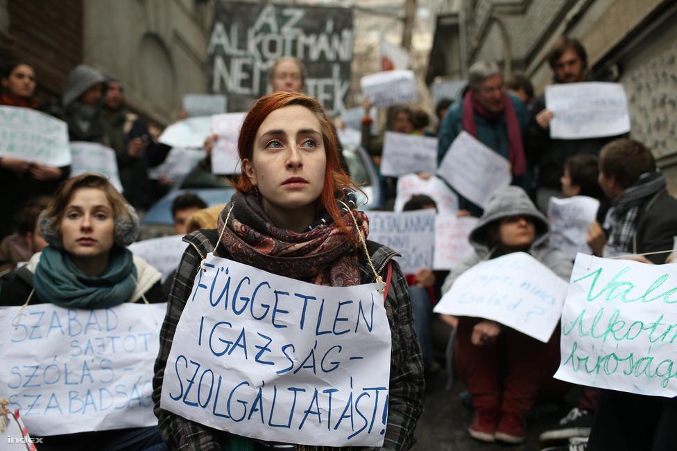 """A Fidesz székháza előtt demonstrált az Alkotmány nem játék! csoport egy erőszakmentes, polgári engedetlenséget is felvállaló akcióval. A rendőrség pénzbírsággal sújtotta őket a gyülekezési jog megsértése miatt. A csoport szerint az Alaptörvény 4. módosításával (az Alkotmánybíróság által korábban alkotmányellenesnek ítélt rendelkezések """"Alaptörvénybe"""" írásával és az Alkotmánybíróság jogköreinek további szűkítésével) megszűnt Magyarországon az alkotmányos demokrácia. A megmozdulás aktivistái több mit tíz órán át foglalták el a Fidesz Lendvay utcai székházának udvarát és előterét."""