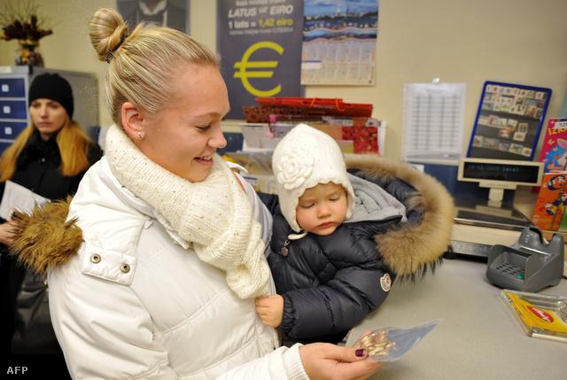 """Euró """"kezdőcsomagot"""" vesz át egy nő gyerekével egy rigai postán"""