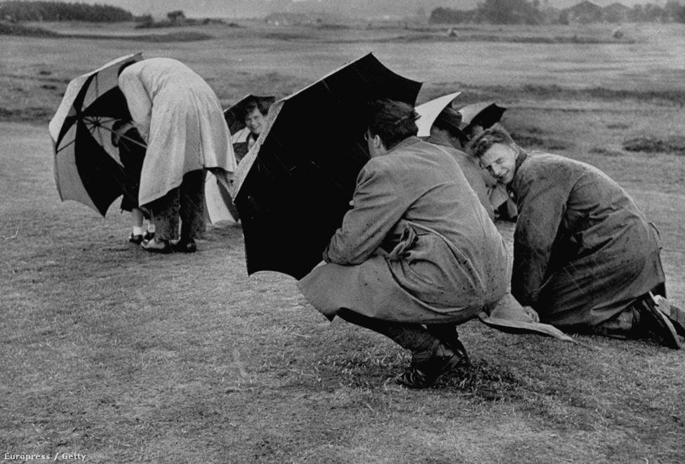 Az erős eső elől az esernyők alá menekülnek a British Open nézői.