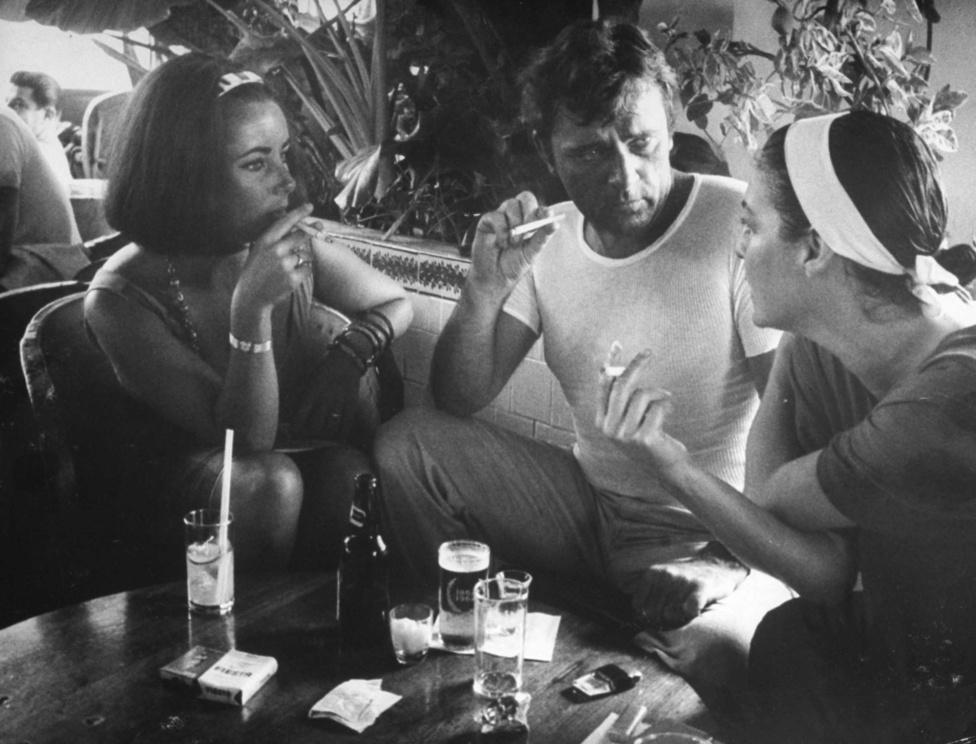Gjon Mili Az iguána éjszakája című filmről 1963-ban  tudósított a LIFE magazinnak. A képen Elizabeth Taylor, Richard Burton és Ava Gardner cigiznek a forgatás szünetében. Taylor nem szerepelt a filmben, csak Burtont látogatta meg. Puerto Vallartában forgattak, amiről a forgatás előtt senki sem hallott, Taylor és Burton tartózkodása tette fel a térképre, ma már népszerű üdülőhely.