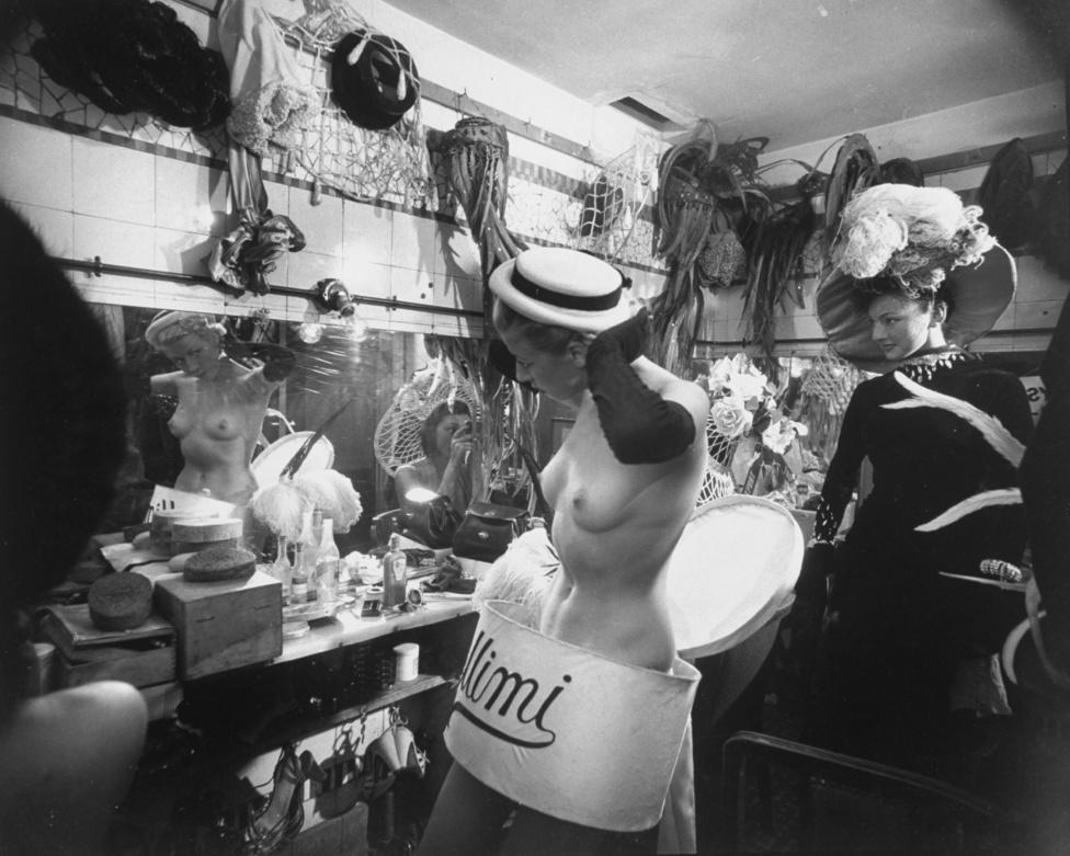 Mili imádta a táncosokat fotózni, legyen szó jégtáncról, balettról vagy revüről, a mozgást próbálta megörökíteni. Ezen a képen táncosnők öltöznek a Lido klubban, a kalapot és Mimi feliratot viselő hölgy még az öltözés elején tart.